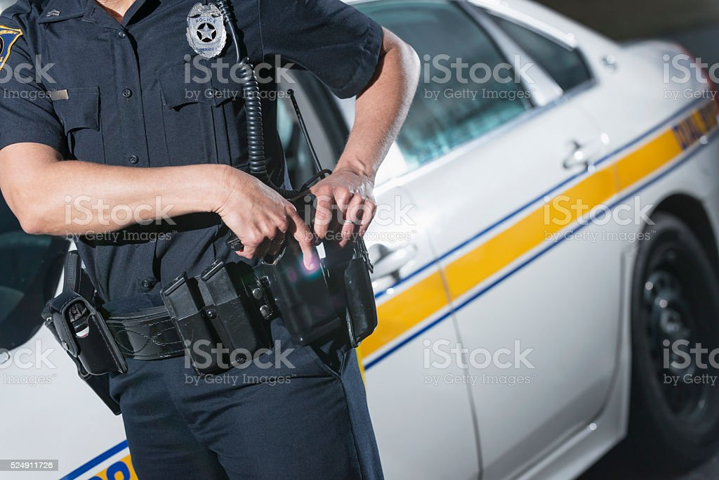 Cropped view of policewoman by patrol car, hand on gun stock photo