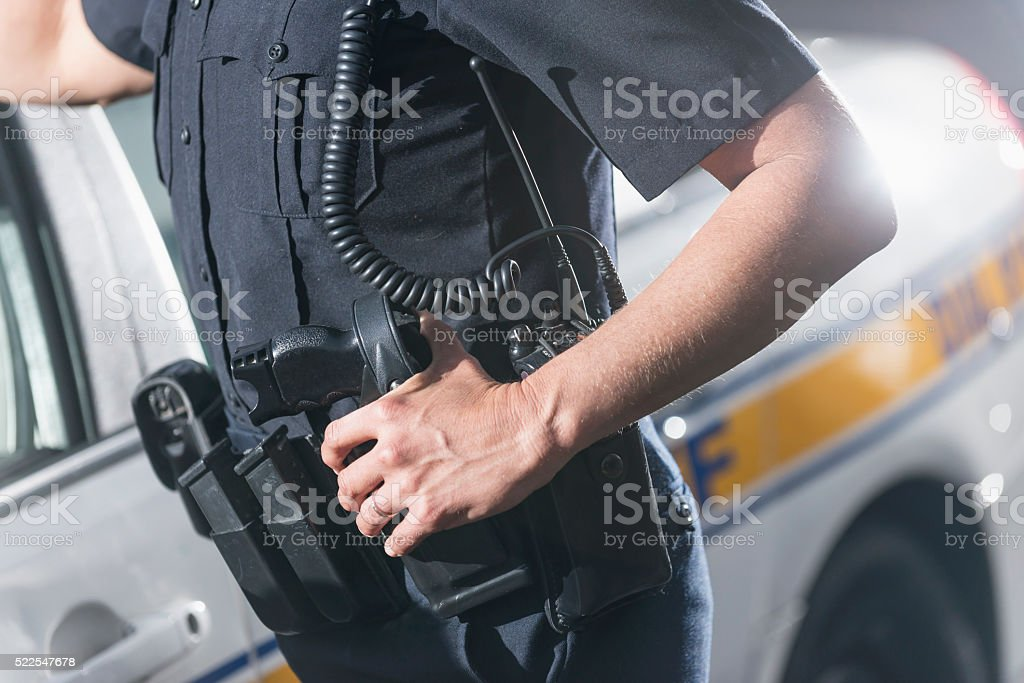 Cropped view of policewoman next to patrol car stock photo