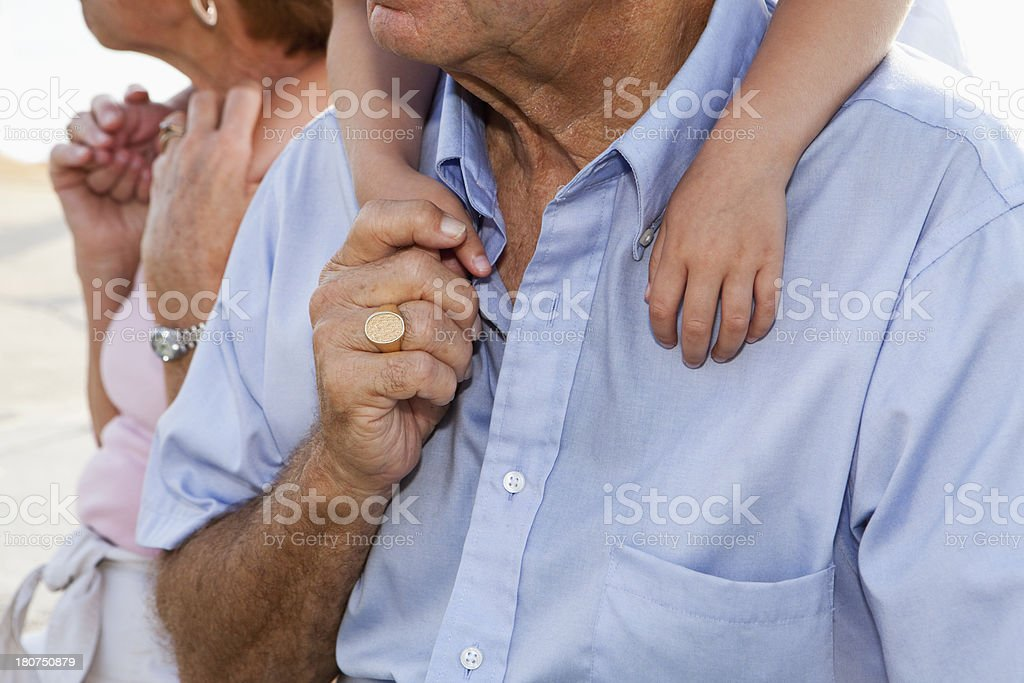 Cropped view of senior couple with grandchildren on back stock photo