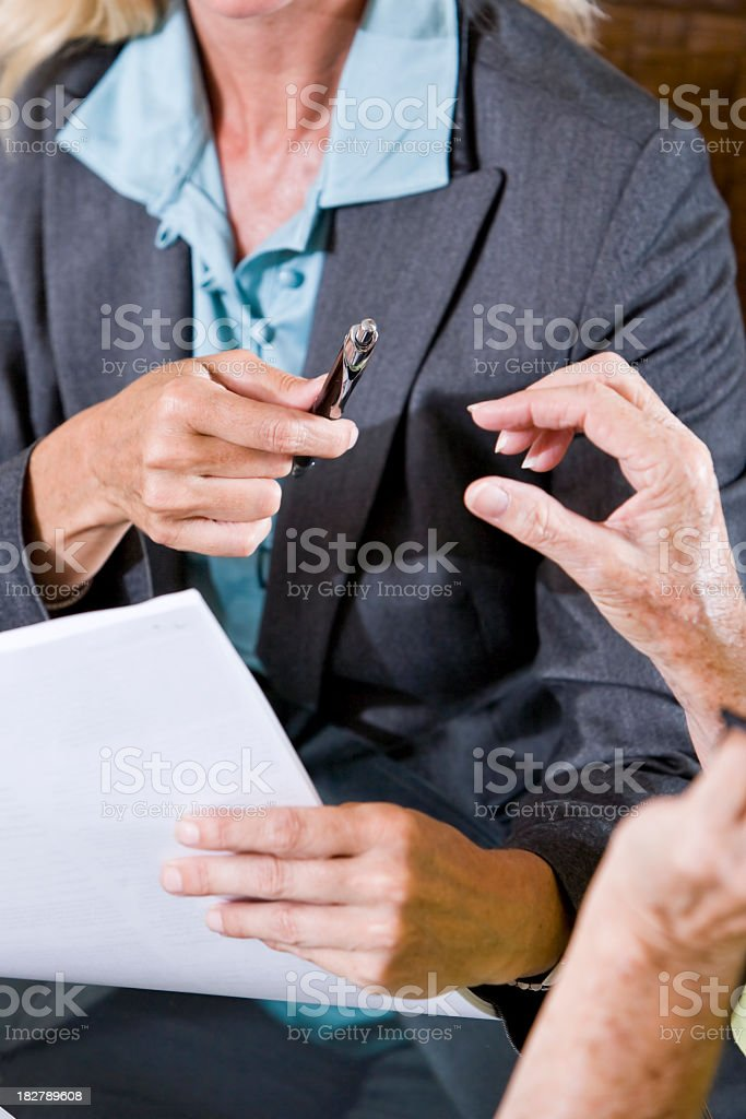 Cropped view of senior woman taking pen to sign document royalty-free stock photo