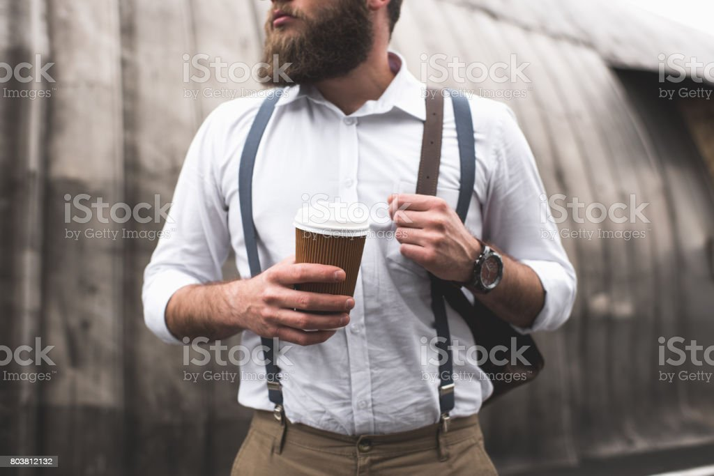 cropped view of stylish bearded man on coffee break holding disposable cup stock photo