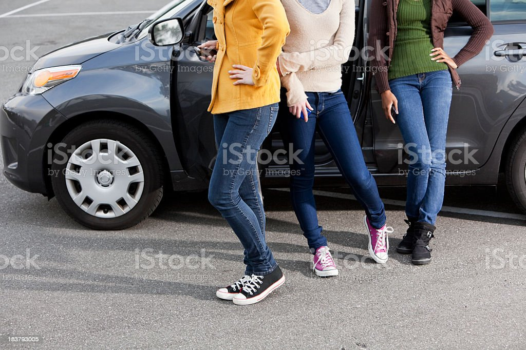 Cropped view of teenage girls by car stock photo