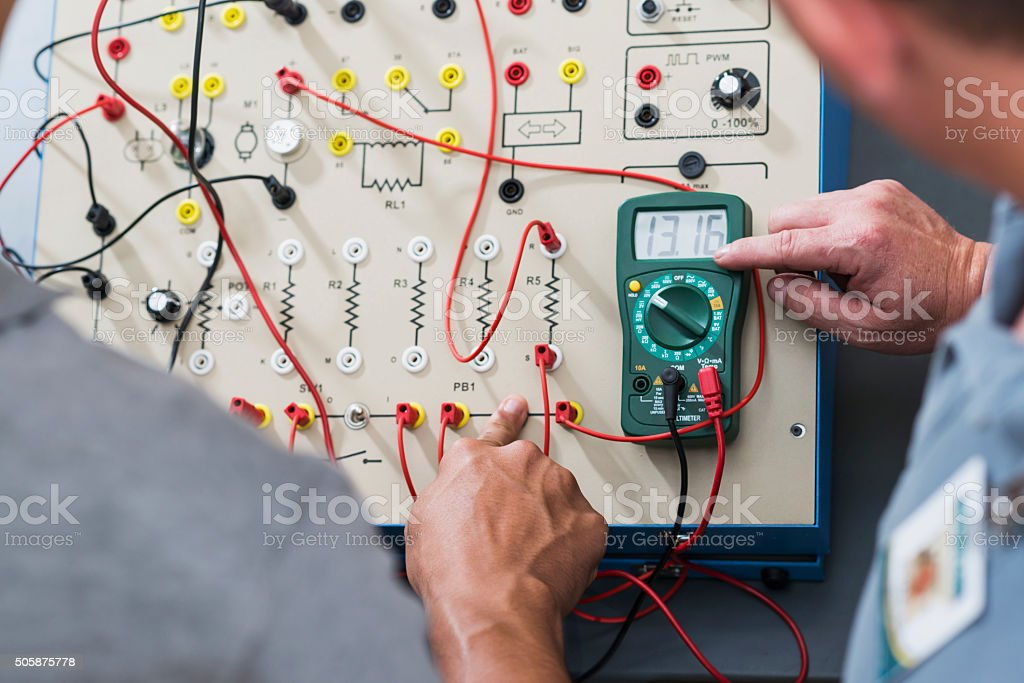 Cropped view of trainees using electrical circuit board stock photo