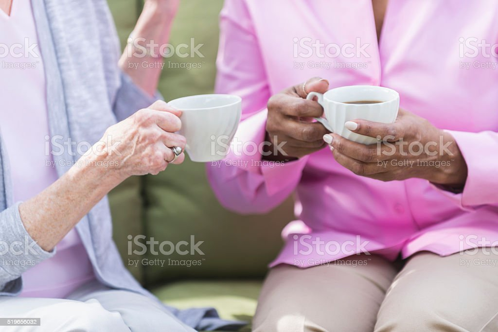 Cropped view of two senior women talking over coffee stock photo
