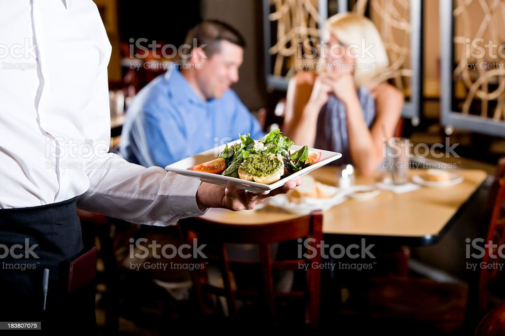 Cropped view of waiter holding salad plate in restaurant royalty-free stock photo