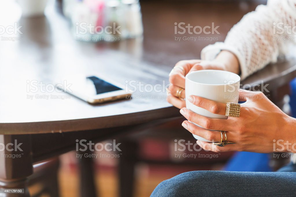 Cropped view of woman at table holding cup stock photo