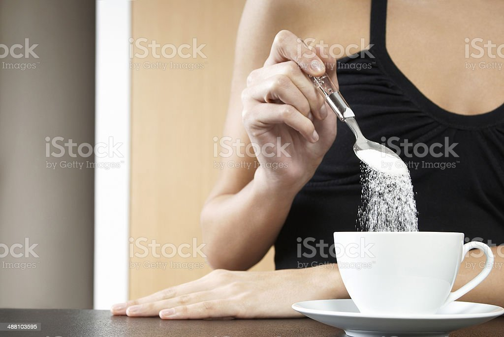 Cropped Woman Pouring Sugar In Tea Cup stock photo