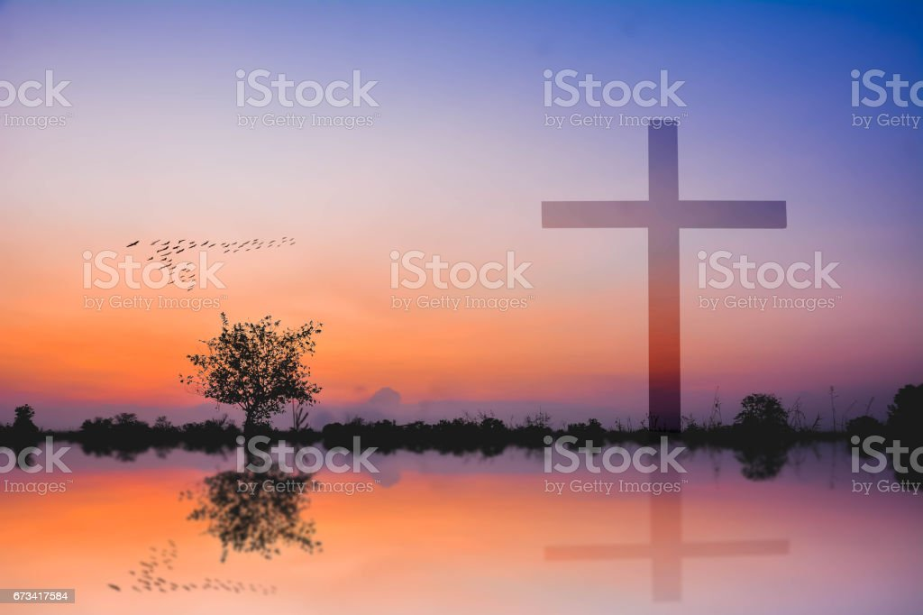 cross against mountain and lake view at sunset stock photo