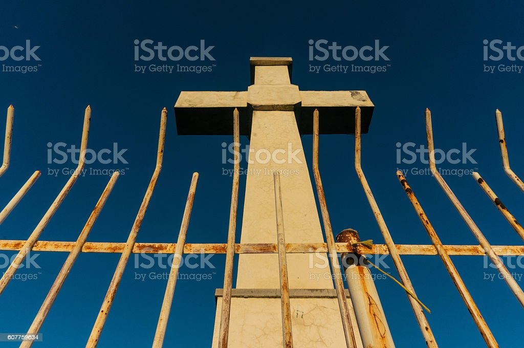 Cross behind fence stock photo