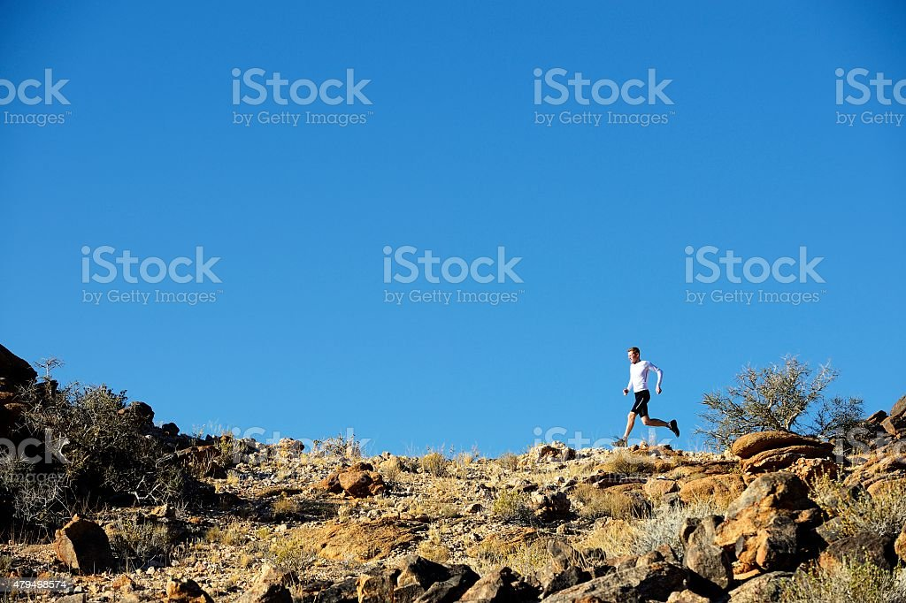 Cross country runner etched against blue sky stock photo