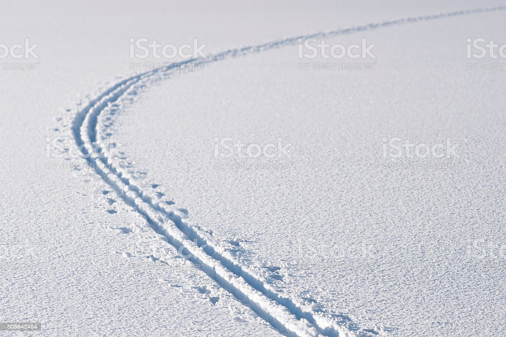 Cross country ski tracks in snow on frozen lake stock photo