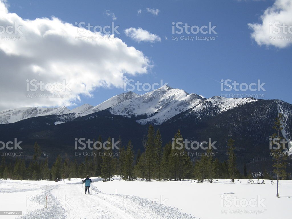 Cross Country Skier with Snow Capped Mountain stock photo