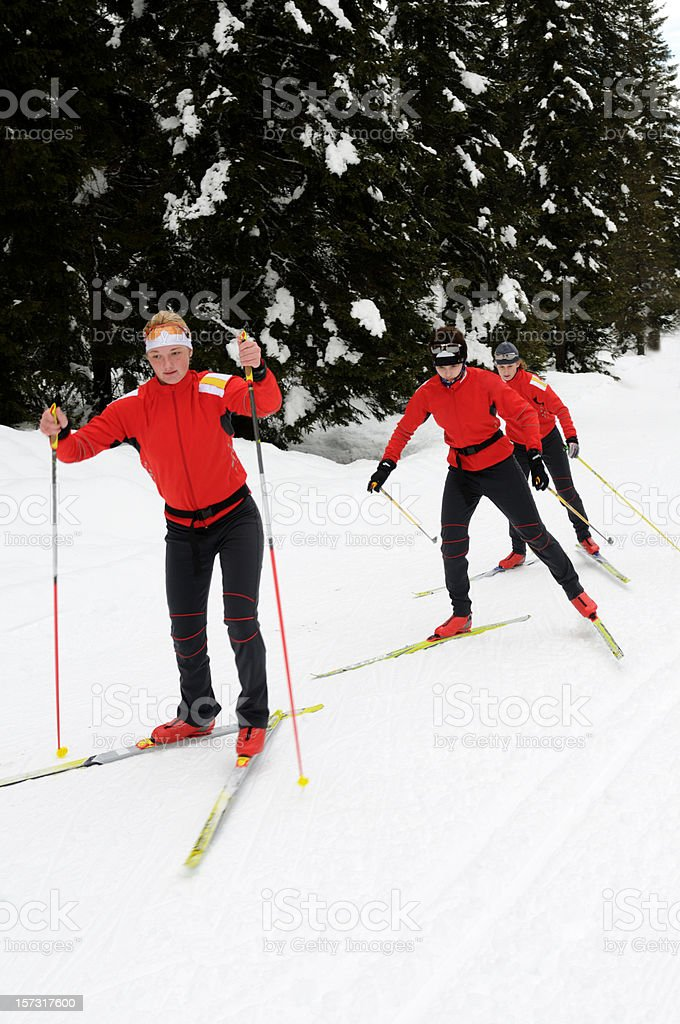 Three young cross country skiers running through the forest, skating...