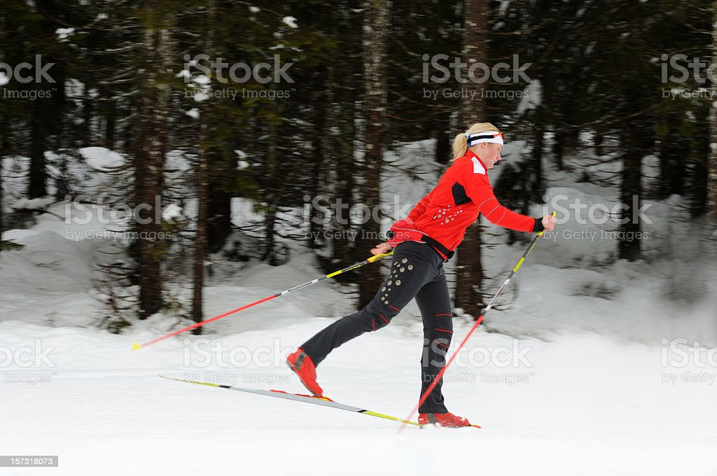 Beautiful female cross country skier running through the forest,...