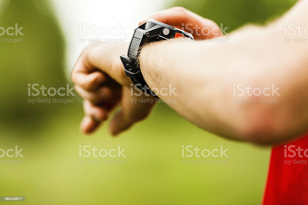Cross country trail runner looking at sport watch stock photo