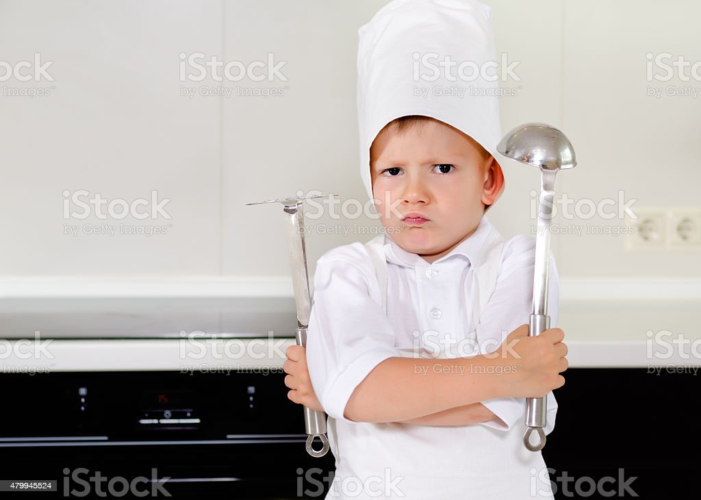Cross determined little boy chef stock photo
