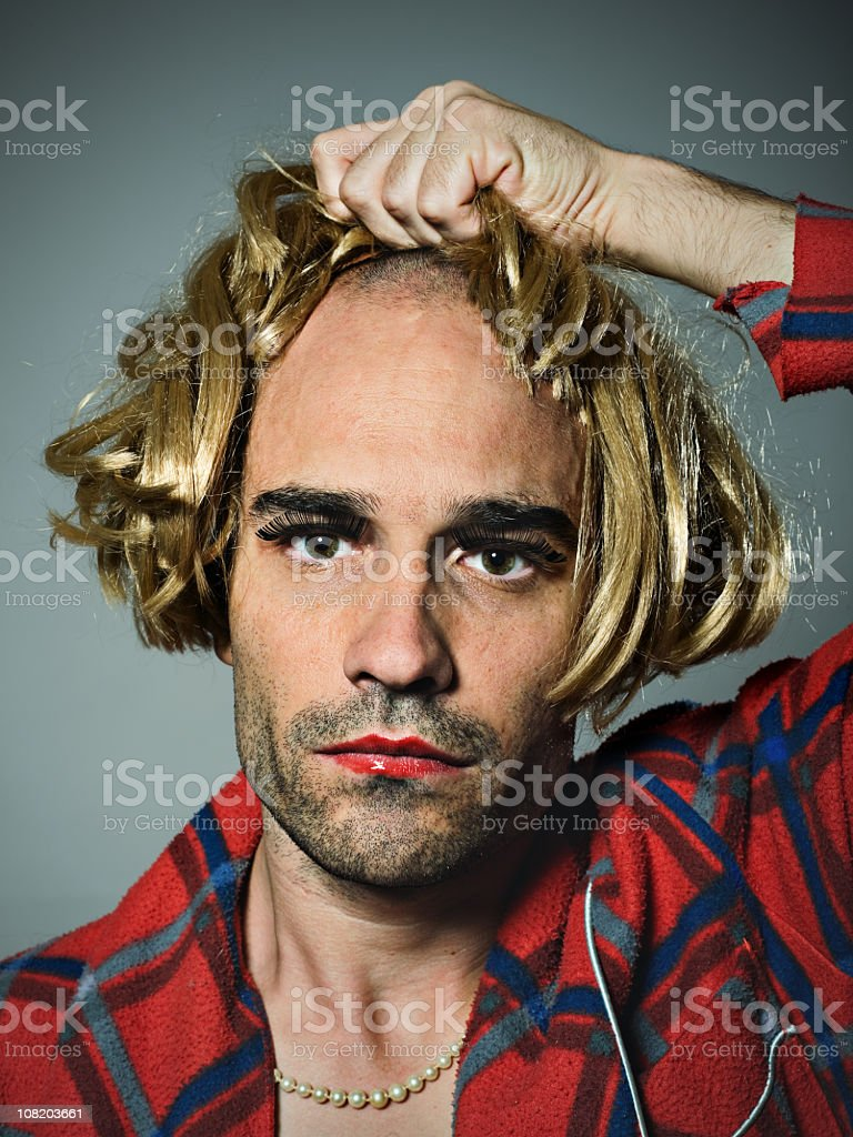 Cross Dressed Man Putting on Wig stock photo