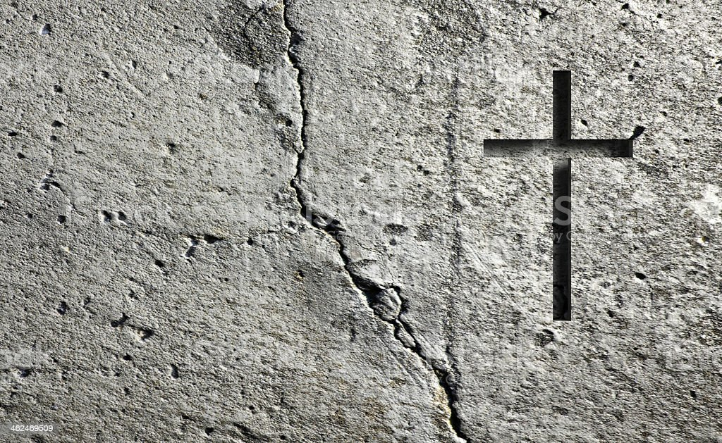 A cross engraved into a old wall stock photo