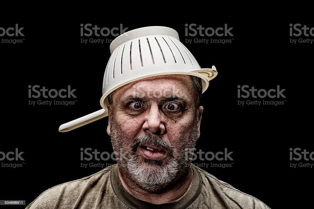 Cross Eyed Crazy Guy wearing a colander as a hat stock photo