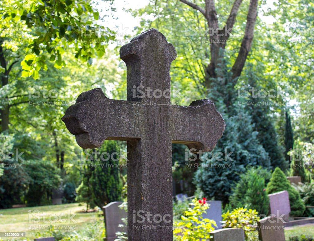 Cross in cemetery around woodland area stock photo
