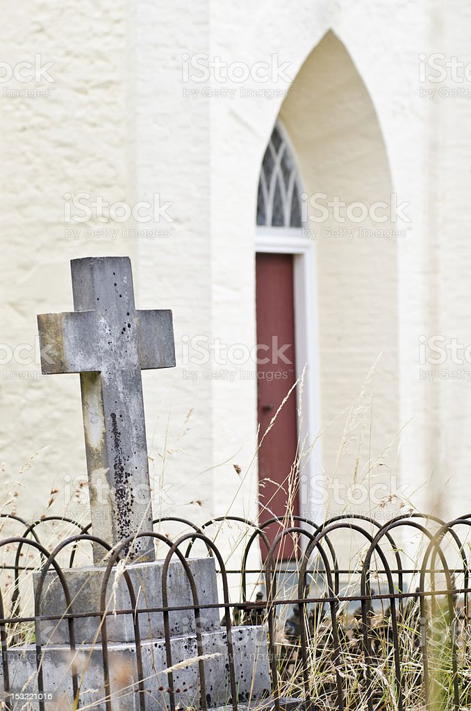 Cross in cemetery near church royalty-free stock photo
