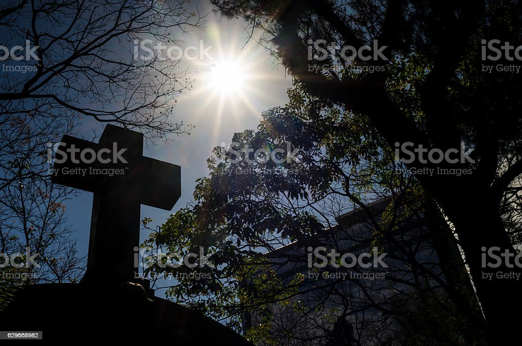 Cross in cemetery under the sun stock photo