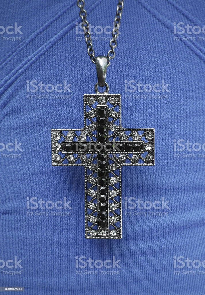 Cross necklace on blue shirt royalty-free stock photo