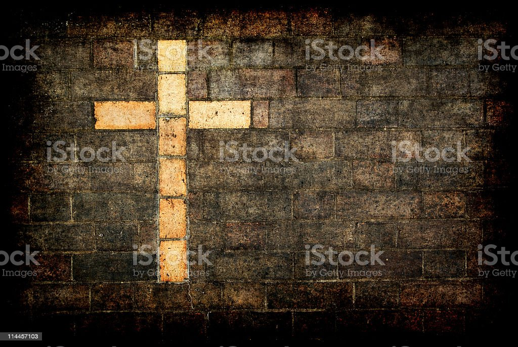 cross of christ built into a brick wall stock photo