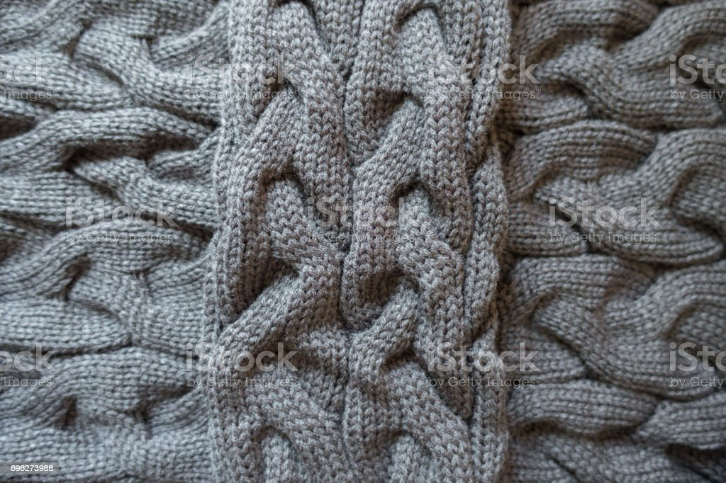 Cross of grey knit fabric with plait pattern stock photo