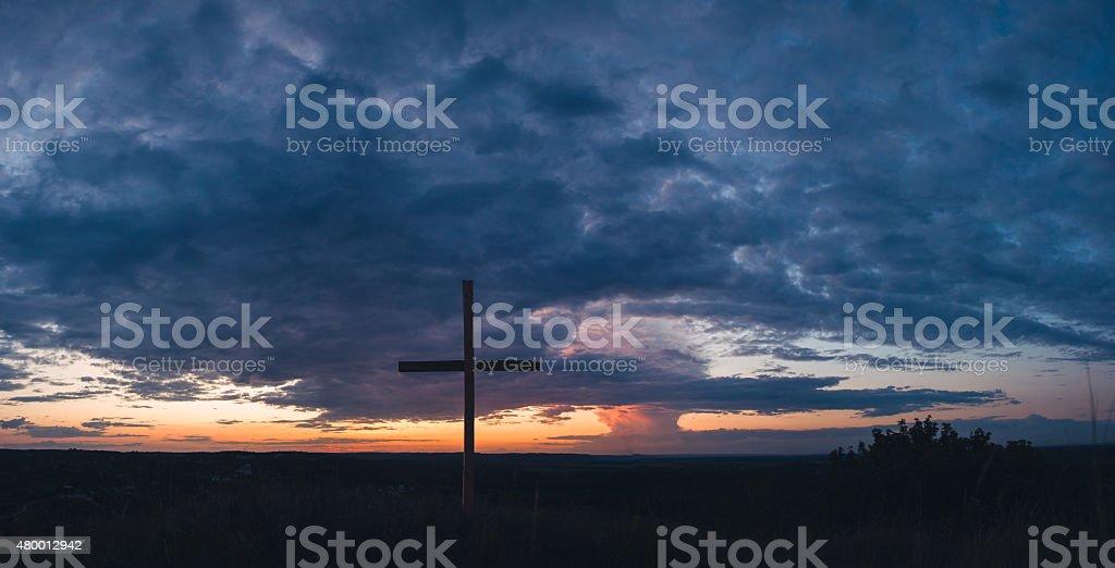 Cross on background of beautiful dramatic sky at sunset stock photo