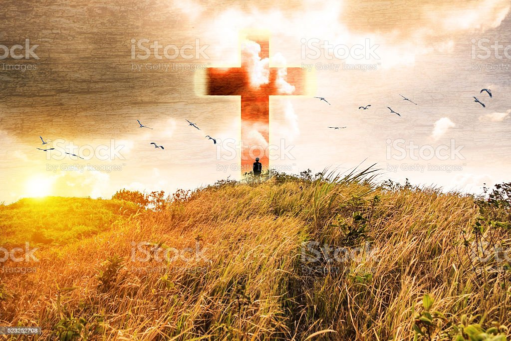 Cross on gold meadow mountain shining light stock photo