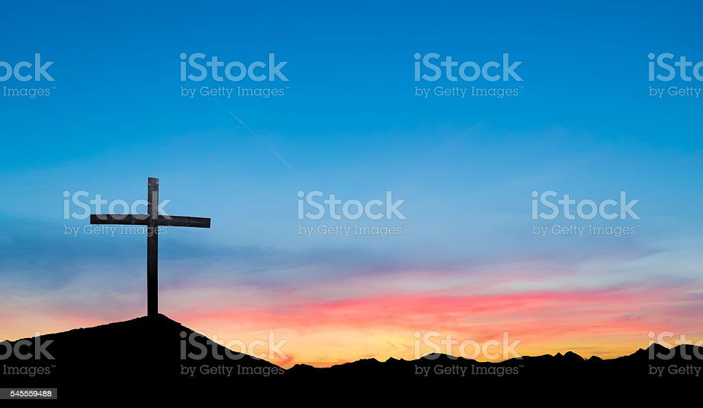 Cross on hill at sunset or sunrise stock photo