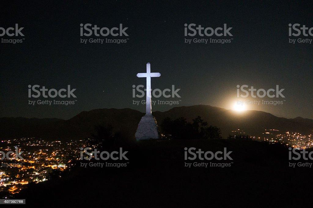Cross on Mountain Overlooking Valley with Supermoon Rising stock photo