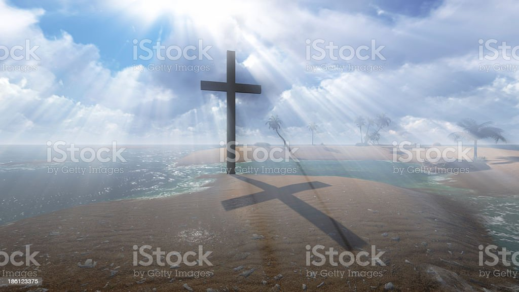 Cross on the beach under a beaming sunset stock photo