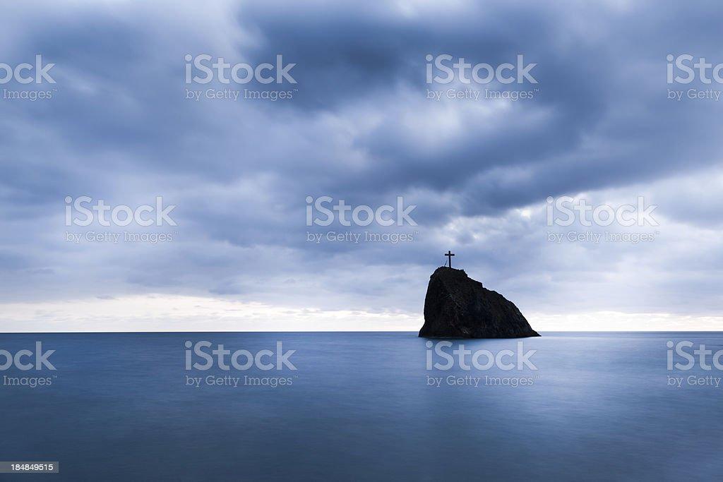 Cross on the rock stock photo