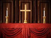 Cross shape and lit candles  on red velvet