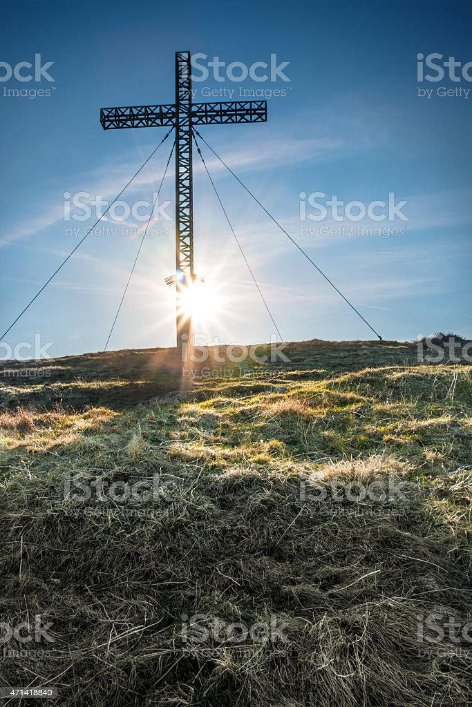 Cross shape front of sunlight glow on hill top mountain stock photo