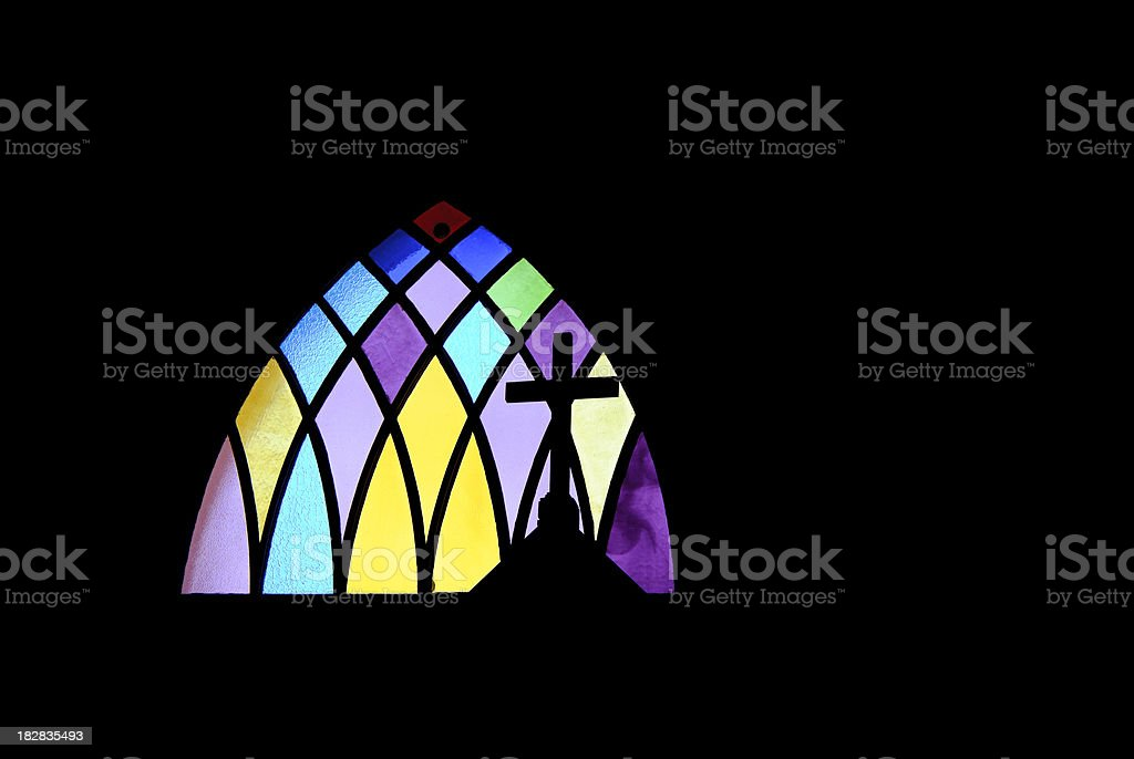 Cross Silhouetted on Stained Glass stock photo