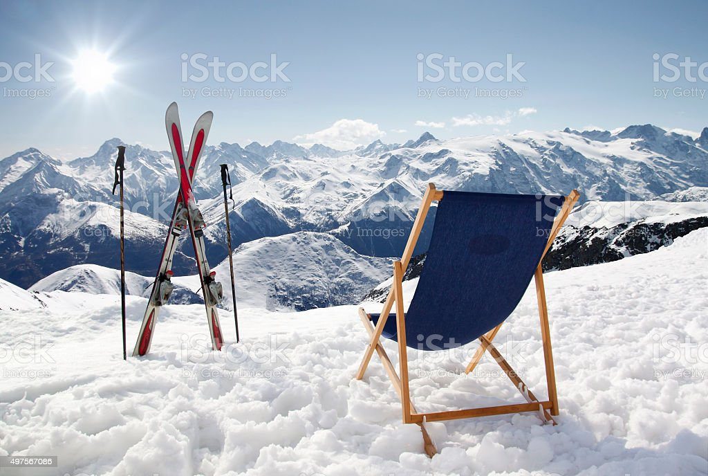 Cross ski and Empty sun-lounger at mountains in winter stock photo