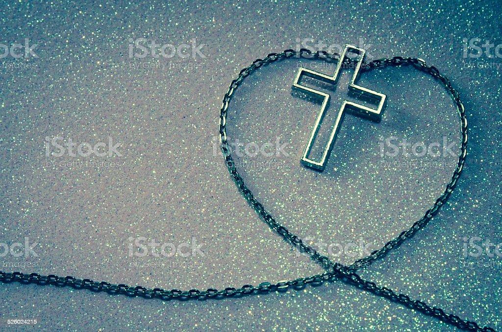 cross symbol in chain love shape stock photo