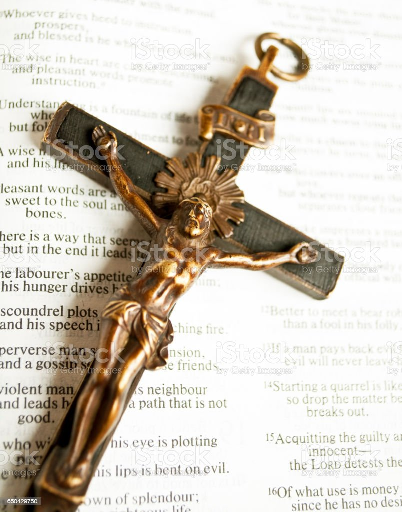 Cross with crucified Jesus Christ on open bible stock photo