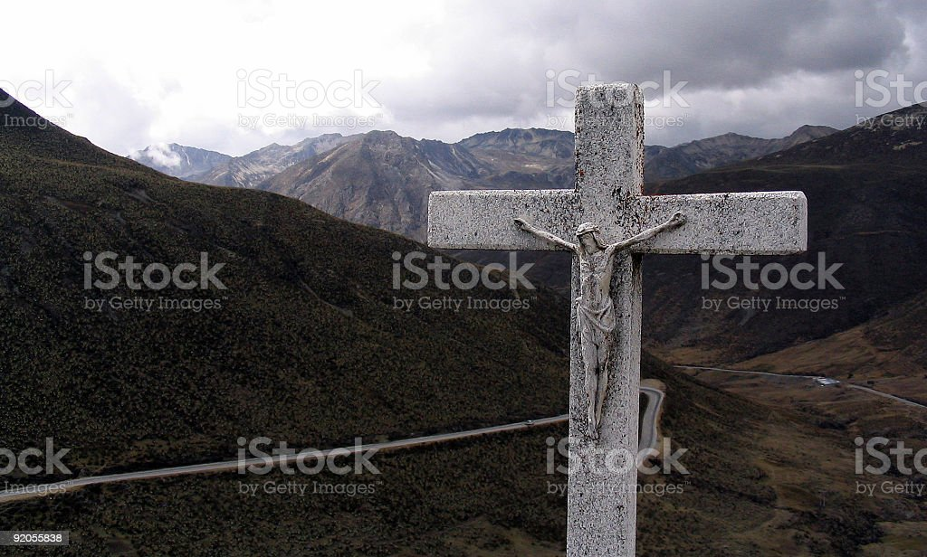 Cross with Jezus in mountain scenery stock photo