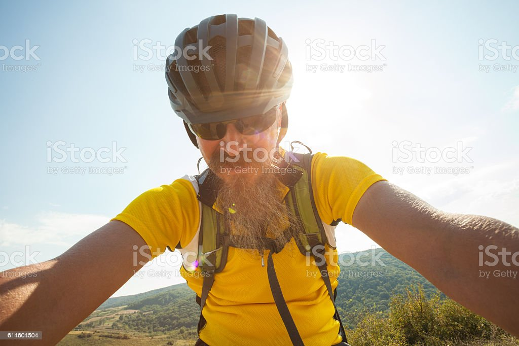 Crosscountry cycling; man riding mountain bicycle uphill stock photo