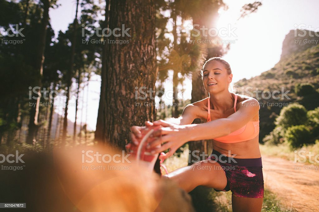 Cross-country runner doing her warm-up on nature trail mountain stock photo
