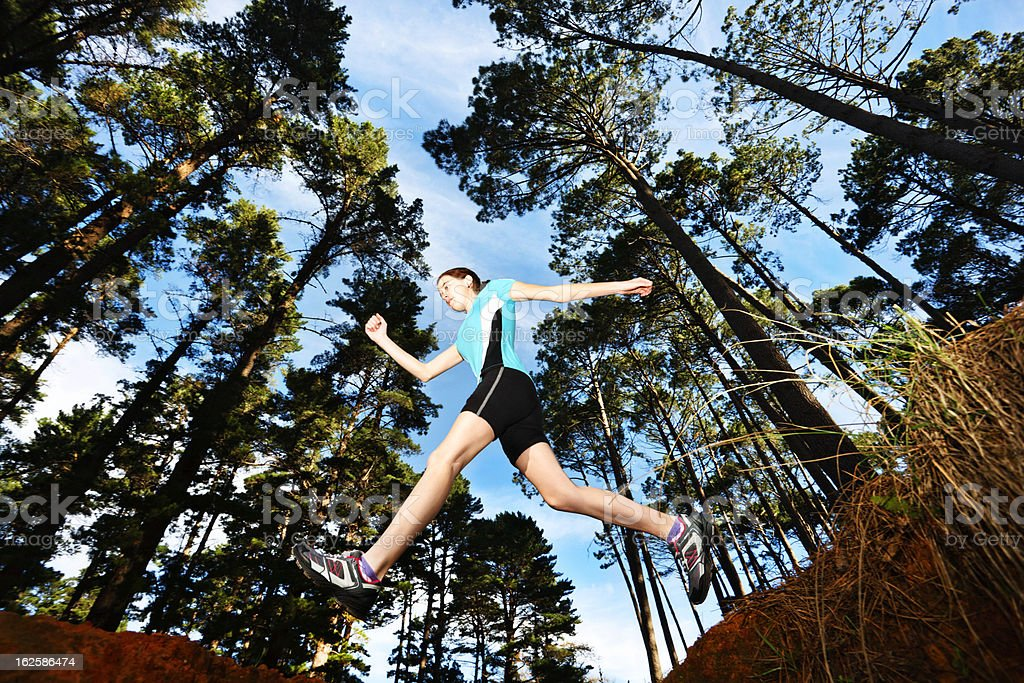 Cross-country runner is airborne as she leaps a forest ditch royalty-free stock photo
