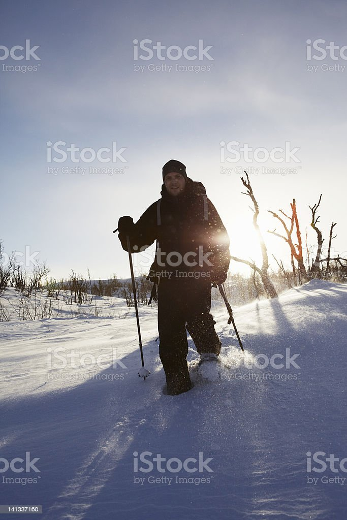 Cross-country skier walking in snow stock photo