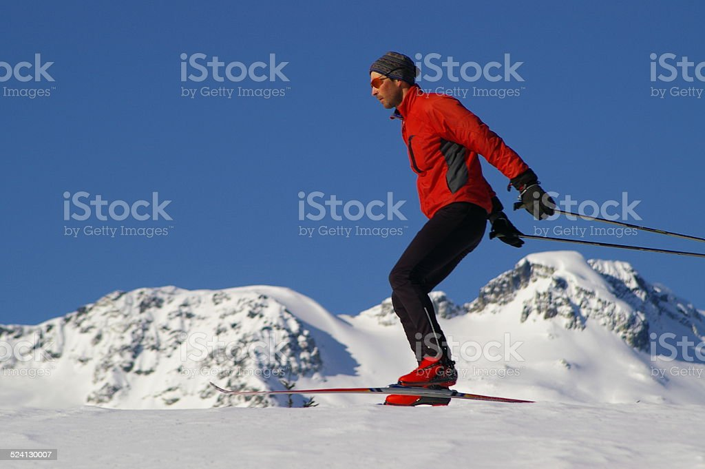 Crosscountry skier with snow covered mountain background stock photo