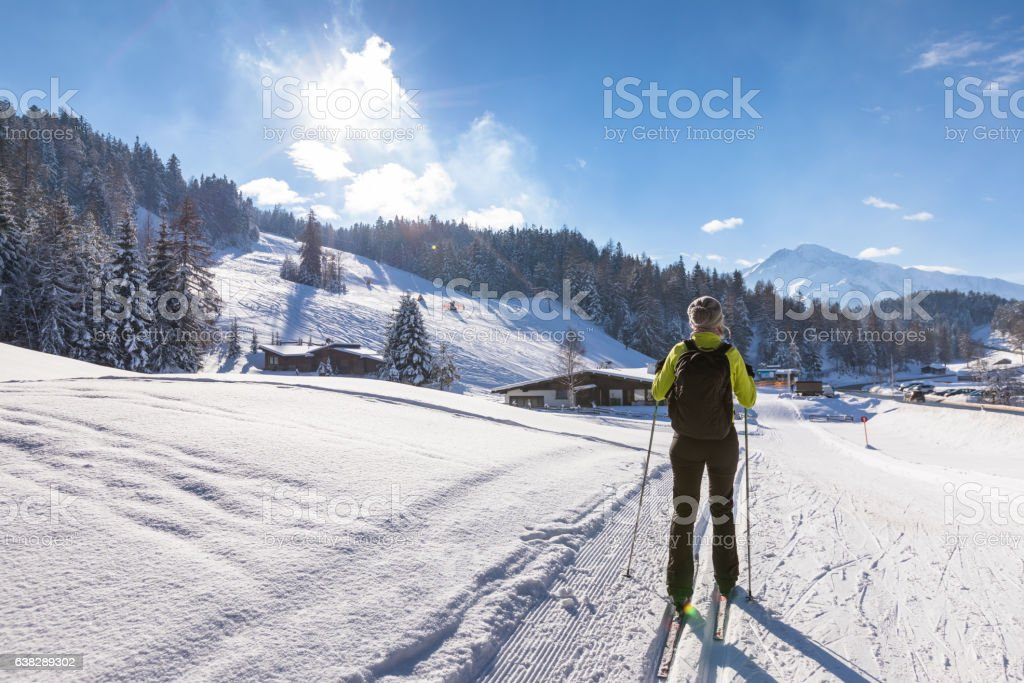 Cross-country skiing in sunny winter landscape, beautiful mountains in background stock photo