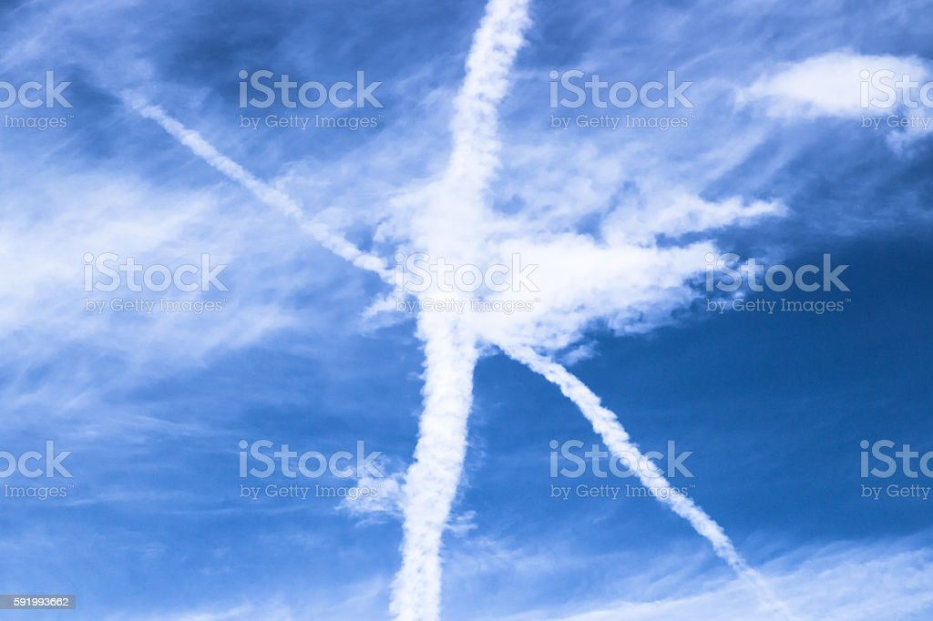 Crossed chemtrails on sky stock photo