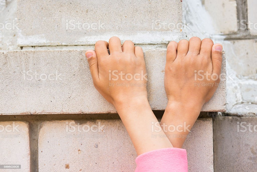 Crossed children's hands seized on the brick wall stock photo
